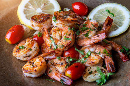 Grilled spicey shrimps with seasoning and vegetables. Banco de Imagens