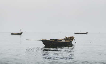 Wooden fishery boats in the sea with fog 