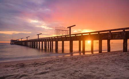 Long sea bridge in the sunset time with warm low lighting and dark shadow. 版權商用圖片
