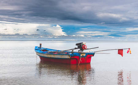 Fishery wooden boats with outdoor sun lighting and dark cloud sky.