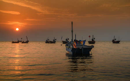 Small fisherman boats in the sea with sunset and warm low lighting and dark shadow. Banco de Imagens