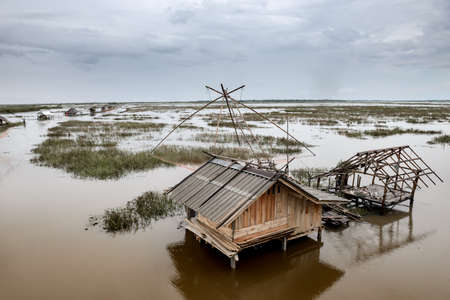 Fisherman cottage in swamp and square dip fish trap with cloudy raining low lighting.