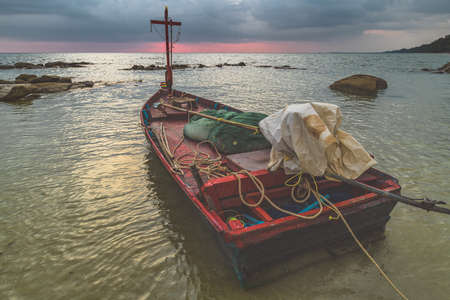 Wooden fishery boat in the sea with outdoor sun lighting and cloudy sky. 版權商用圖片