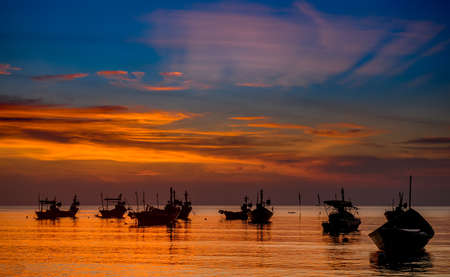 Silhouette fishery boats in the sea with sunset warm low lighting and dark shadow.