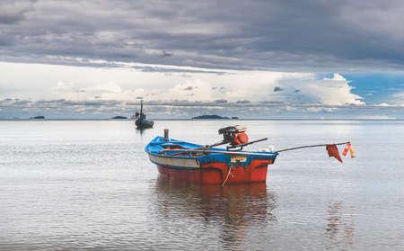 Fishery wooden boats with outdoor sun lighting and dark cloud sky. 版權商用圖片 - 163963017