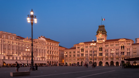 Piazza dell'Unita in Trieste with Palazzo del Municipio shot at sunset in soft pink light 스톡 콘텐츠