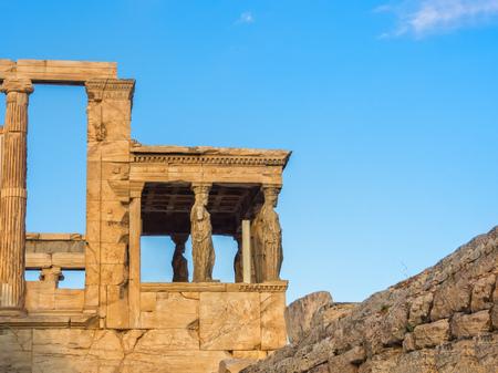 Porch of Poseidon temple, part of Erechtheion, sacred olive tree, walls of temple of Athena Polias on Acropolis, Athens, Greece against blue sky