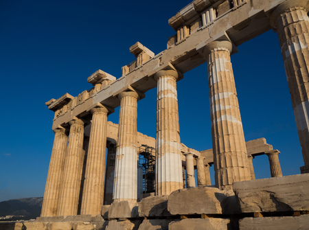 Columns of Parthenon temple on Acropolis of Athens, Greece at sunset against blue sky