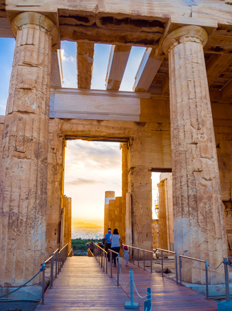 Columns of Propylaea entrance gateway of Acropolis, Athens, Greece overlooking the sunset and city