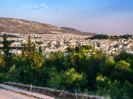 View of Athens, Greece, against hills and greenery at sunset