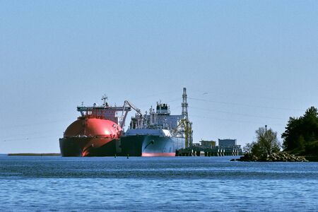 LNG or liquified natural gas tanker and LNG carrier used as floating LNG storage and regasification unit and import terminal in port on sunny day in Klaipeda, Lithuania. Alternative gas supply, commecial freight, energy crisis, diversification