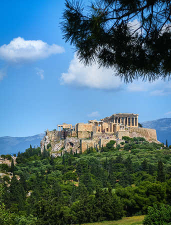 Great view of Acropolis hill from Pnyx hill on summer day with great clouds in blue sky, Athens, Greece. Propylaea, Parthenon.
