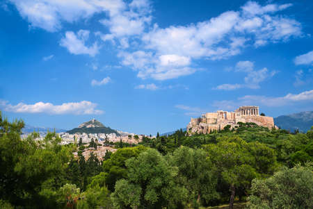 Iconic view of Acropolis hill and Lycabettus hill in background in Athens, Greece from Pnyx hill in summer daylight with great clouds in blue sky.