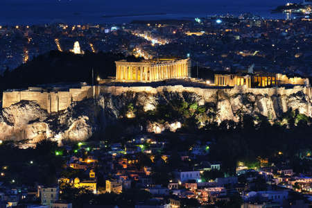 Close view of Acropolis Parthenon and Erechtheion, Philoppapos monument at night. City lights of Athens.