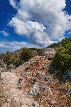 Greek or Cretan landscape, hills with spring foliage, bushes, olive trees, rocky path, mitato. Blue sky with clouds. Akrotiri, Chania, Crete, Greece