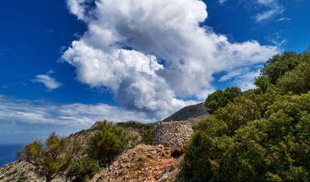 Typical Greek landscape, hill, mountain, spring foliage, bush, olive tree, rocky path. Blue sky with beautiful clouds. Akrotiri, Chania, Crete, Greece