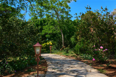 Gardening design ideas. Natural pavers, paths, decorations, lanterns. Rich foliage, bushes and trees. Winding paths, open soil, no mulch. Daytime shot