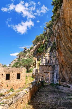 Ruins of entrance gate to abandoned Orthodox Katholiko monastery in Avlaki gorge, Akrotiri peninsula, Chania, Crete, Greece. Spring daytime. Reklamní fotografie