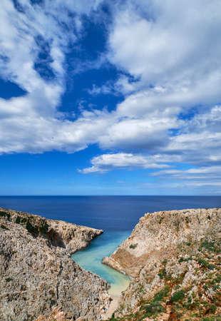 Vertical view of z-shaped cove in Greek or Cretan landscape on sunny day. Blue sky, beautiful clouds. Seitan Limania, Akrotiri, Crete island, Greece