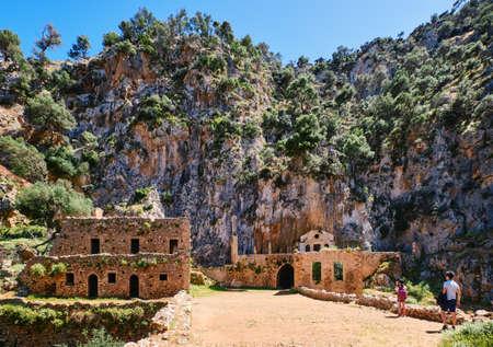 Ruins of remote abandoned Orthodox Katholiko monastery and bridge, Avlaki gorge, Akrotiri peninsula, Chania, Crete, Greece. Tourists explore the area