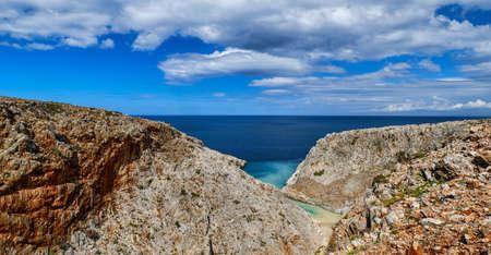 Rocky red cliffs of typical Greek view, azure sea, clear blue sky, beautiful sky. Stefanou beach, Seitan Limania, Akrotiri peninsula, Crete, Greece