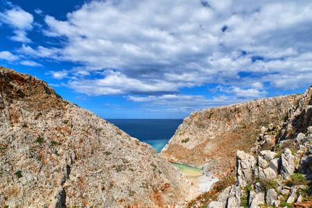 Rocky red cliffs, blue sea, clear blue sky and beautiful sky. Stefanou beach, Seitan Limania, Akrotiri peninsula, Chania region, Crete island, Greece