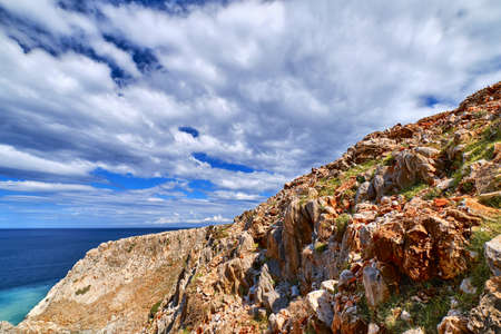 Beautiful wild red cliffs against clear blue sky and dynamic clouds. Diagonal compositition. Typical Greek or Cretan landscape. Mediterranean islands.