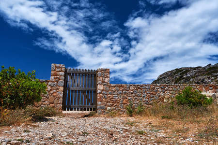 Countryside landscape. Rustic stone wall fence and aged black timber wicket door. Great blue sky with awesome clouds.