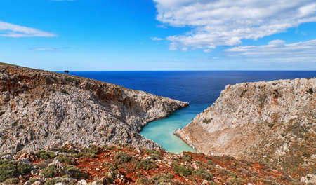 View of z-shaped bay, blue sky, beautiful clouds, sunny day, azure sea. Red soil in foreground. Stefanou beach, Seitan Limania, Crete island, Greece