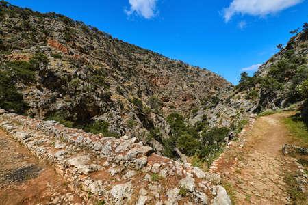 Dynamic composition of typical Greek landscape, hills, fresh spring greenery, paved paths crossing. Avlaki gorge of Akrotiri, Chania, Crete, Greece