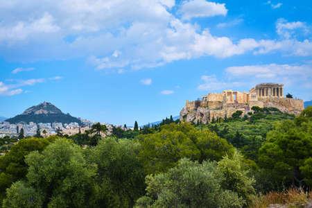Iconic vew of Acropolis hill and Lycabettus hill in background in Athens, Greece from Pnyx hill in summer daylight with great clouds in blue sky.