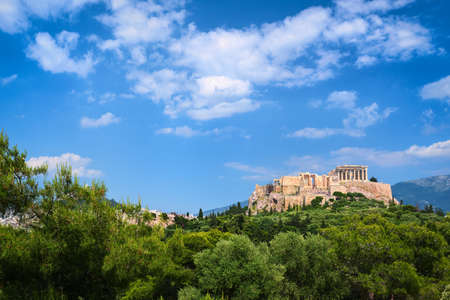 Beautiful view of Acropolis hill in Athens, Greece from Pnyx hill in summer day with great clouds in blue sky. Famous ancient UNESCO heritage site