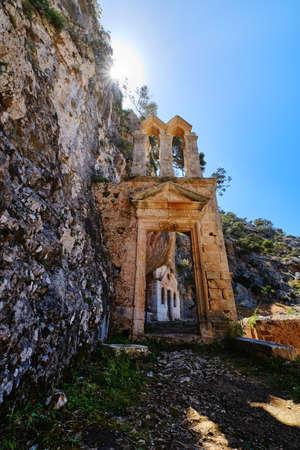 Ruins of abandoned Orthodox Katholiko monastery in Avlaki gorge, Akrotiri, Chania, Crete, Greece. Entrance gate. Upshot against sun. Spring daytime