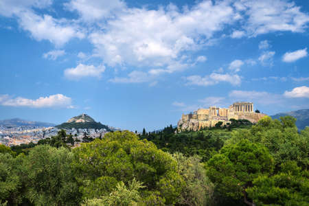Iconic view of Acropolis hill and Lycabettus hill in background in Athens, Greece from Pnyx hill in summer daylight with great clouds in blue sky. Reklamní fotografie