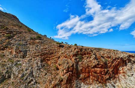 Beautiful wild red cliffs, clear blue sky, clouds. Diagonal view. Typical Greek landscape. Akrotiri peninsula, Chania region, Crete island, Greece