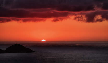 Beautiful sunset in red and purple over sea under heavy stormy clouds. Sun touching horizon.
