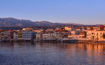 Sunrise at Old Venetian harbour of Chania, Crete, Greece, shop, hotels, cafes and restaurants on its quay in first sunrays. Cretan hills and mountains