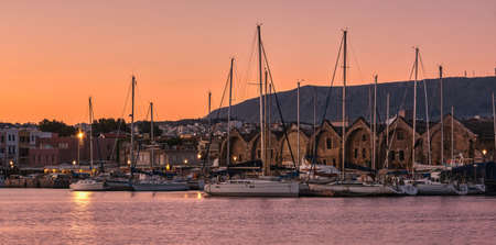 Sunrise over Old Venetian port and harbour of Chania, Crete, Greece. Sailing boats, pier, Old Venetian shipyards and distant Cretan mountains.