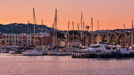Sunrise over Old Venetian harbour of Chania, Crete, Greece. Sailing boats anchored by pier, Old Venetian shipyards or Neoria and Cretan mountains