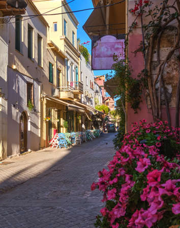 Beautiful view of narrow streets of old town of Chania, Crete, Greece in early morning. Street cafes and restaurants. Selective focus. Pink petunia.