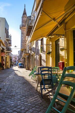 Early morning in old narrow streets of Chania, Crete, Greece and historical monument of Ottoman era - Ahmet aga minaret. Street cafes and restaurant Reklamní fotografie