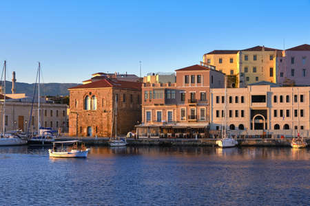 Fishing boat pass by Grand Arsenal in Old Venetian harbour, Chania, Crete, Greece. Sunrise view of quay and sailing boats anchored by piers, cafes.