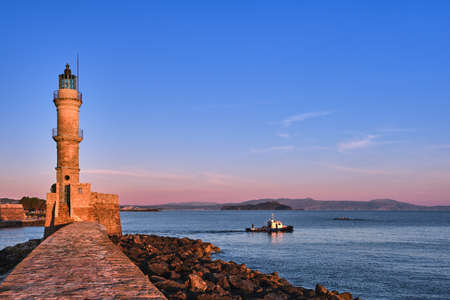 Fishing boat pass by Lighthouse, leave Old Venetian harbour of Chania, Crete, Greece at sunrise. Early morning sky and Cretan hills in distance.