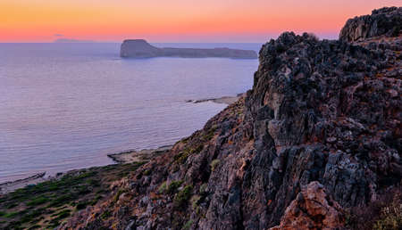 Sunset view of Gramvousa islet behind the rocky hills of Balos beach area, Crete, Greece.