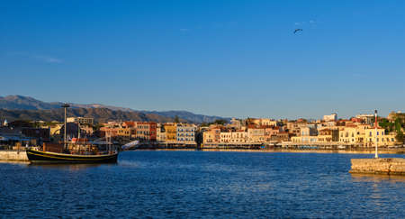 Beautiful view of Old Venetian harbour of Chania, Crete, Greece, quayside, tourist boats by piers in early morning. Cretan mountains in background.