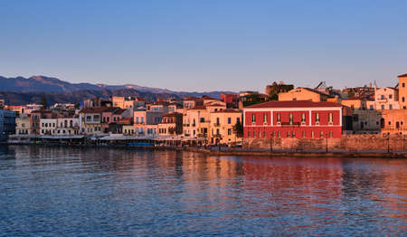 Sunrise view of Old Venetian harbour, Chania, Crete, Greece, its quay.Maritime museum of Crete in first sunrays. Cretan hills and mountains