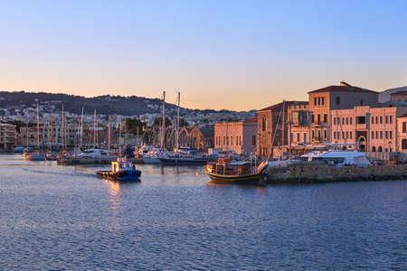 Fishing boat leaving Old Venetian port of Chania, Crete, Greece at sunrise. Sailboats, yachts, Grand Arsenal, Old Venetian shipyards or Neoria Reklamní fotografie