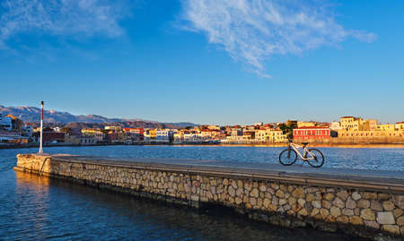 Early morning in Old Venetian port of Chania, Crete, Greece. Pier and bicycle in foreground. Quayside and Cretan mountains. Healthy lifestyle.