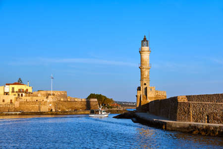 Fishing boat pass by famous Lighthouse and walls of old port, Firka fortress, Old Venetian harbour of Chania, Crete, Greece in morning. Golden hour Reklamní fotografie