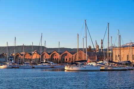 Sunrise in Old Venetian port, Chania, Crete, Greece. Sailing boats, yachts, pier, Old Venetian shipyard. Bell tower of Greek church, Cretan mountains